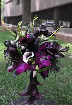 This wild bouquet highlights a calla lily handle accent, black feathers, fern shoots and dendrobium orchids.