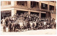 A photo postcard, which shows a large group photo of the men who built the Pemberton Block in Victoria, located at 637-649 Fort Street in Victoria. Some are posed in the windows above as well. The building changed names after industrialist Norman Yarrow bought the building in 1913. Card is published by Shaw Bros.