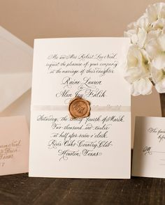 Custom calligraphy is engraved into this suite that features gold edging and a wax-seal belly band.Atheneum Creative