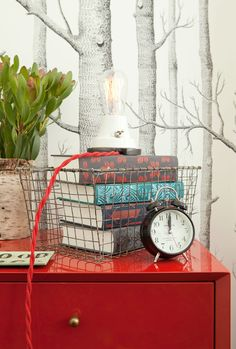 Jenny Wolf Interiors - Glossy red lacquer dresser, Cole & Son Woods wallpaper, vintage, books in wire basket . Hall Wallpaper, Wood Wallpaper, Red Nightstand, Bedside Clock, Dresser, Small Study Table, Vintage Wire Baskets, Modern Rustic Homes, Cole And Son
