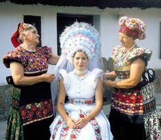 """Mezőkövesdi matyó menyasszonyi viselet  Tájegység: Matyó Régió: Mezőkövesd A mezőkövesdi menyasszonyok 1920–1953 közötti időszakban viselt menyasszonyi öltözete. A fején fehér és színes papírvirágokból készített művirág koszorú, ezüst rezgőkkel és fátyollal. Öltözete fehér selyemből készült aljazatlan szoknya és rövid ujjú, színes pántlikával díszített """"litya"""", """"fellökő"""" blúz. A blúz felett fehér rojtos gyapjúkendő. A szoknya előtt fehér selyemből készült, aprón ráncolt bőkötő, előtte négy…"""