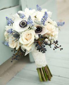 {Ivory Roses, White Anemones, Blue Grape Hyacinth, Blue Eryngium Thistle, Dark Blue Berries, Silver Brunia, & Dusty Miller Hand Tied With Beautiful Ivory Lace}