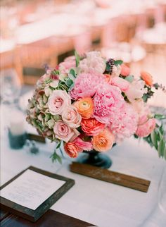 Coral and pink lush centerpiece of peonies and ranunculus