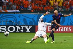 Arjen Robben of the Netherlands shoots and scores his teams second goal as Sergio Ramos of Spain defends in the second half during the 2014 FIFA World Cup Brazil Group B match between Spain and Netherlands at Arena Fonte Nova on June 13, 2014 in Salvador, Brazil.