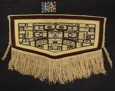 Ceremonial robe: Chilkat/Tlingit. Southeast AK.  Twined weave of mountain goat wool with warp core of shredded cedar bark. Highly conventionalized totemic animal design in yellow, pale green, white & black on brown background. A rectangular face in center with wide base is above face, 2 eyes in black, white, and yellow area above the triangle. Center design: front view of a killer whale while sides and back of the whale & sitting eagle are represented on side panels.    San Diego Museum of…