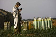 IDF soldier praying next to some serious ammo!