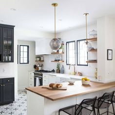 This would be such a lovely way to redo the kitchens in split level homes where the kitchen wall is removed. Love all the wood counters and white and black cabinets and trim.
