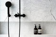 White Statuarietto marble bathroom wall + black shower. (by Dieter Vander Velpen Appartment in Antwerp Belgium Architect)