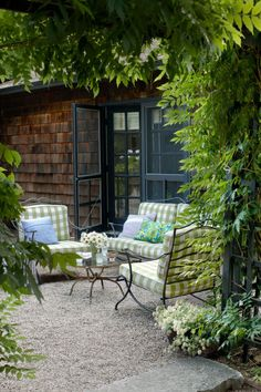 Cushions covered in an outdoor gingham fabric from Scalamandré brighten up the vintage wrought-iron seating on the patio of this Rhode Island retreat.