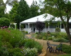 Open Gardens Australia - Curraweena. A pretty cottage style garden enhances this historic cottage beneath a framework of established trees. Gravel paths wind past massed informal plantings of lavender , salvias irises and roses offset by formal hedging,sculptures and well-placed seating.