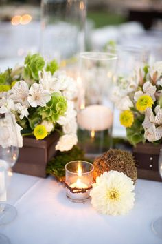 In between the table's bold floral arrangements, place garden flowers in the same coloration. Whites, greens, browns, and a hint of yellow will tie in nicely with the party's garden feel. Floating white candles at varying heights in glass hurricanes will take the guests into the evening.