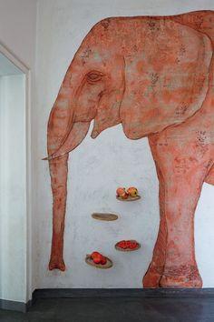 Um elefante feito a partir da raspagem de antigas camadas de papel de parede e de desenho com giz anima a cozinha, que tem ainda velhas raquetes transformadas em prateleiras