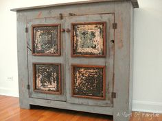 Old cabinet with chippy paint tiles on front.