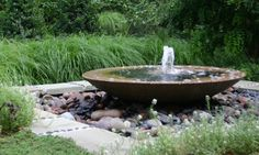 Modern wok fountain on a bed of red river rock