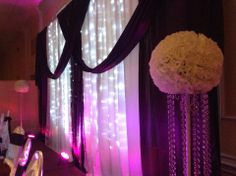 Eggplant backdrop with fairylights and white kissing bals on stands with crystals - a closer look