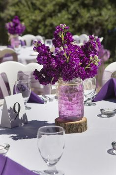 Simple purple stock centerpieces in mason jars w/raffia bows and pink water beads on a wood slab Photo by Farrell Photography