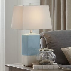Cast a warm glow over your home office or reading nook with this chic table lamp, showcasing a ceramic base and 2-tone finish.