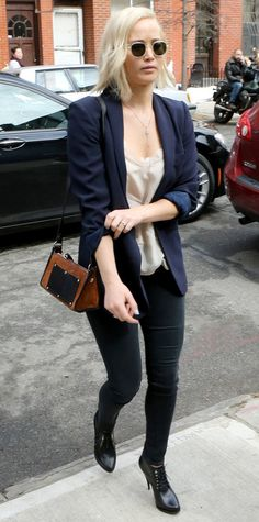 Jennifer Lawrence gave her street style a preppy spin by topping her white tee and dark skinnies with a sharp navy blazer, a structured shoulder bag, and lace-up heeled booties. The finishing touch? Clear shades and a delicate body chain.