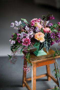 Jewel-toned centerpiece with ranunculus, sweet pea, scabiosa and helleborus by Cincinnati wedding florist Floral Verde.
