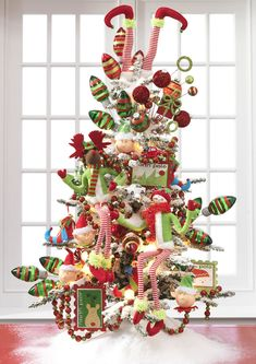 Christmas tree decorated with whimsical polyester elf, snowman, and moose Christmas ornaments