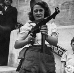 """'Parisian rebel Simone Segouin, also known by her nom de guerre """"Nicole,"""" with a German submachine gun MP-40. She killed an unknown number of Germans and captured 25. She was present at the fall of Chartres, on August 23, 1944, and liberation of Paris. She was promoted to lieutenant, and awarded the Croix de guerre.'"""