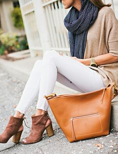 tan sweater, navy blue scarf, white jeans, and brown ankle boots