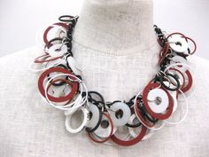 resin and rubber rings attached to a link necklace. Red and black and white. Short necklace with an easy open toggle closing. LIGHT WEIGHT.