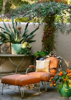 Garden sitting area to just relax. Looks like vintage white wrought iron chair and foot stool.  Faded orange and turquoise are lovely here.