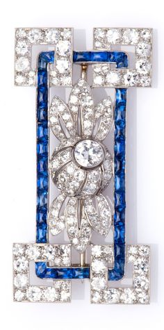 An Art Deco platinum sapphire and diamond brooch, circa 1925.  Composed of square diamond-set corners connected by a band of sugarloaf sapphires, centring a diamond-set flower head, French marks for platinum, numbered. #ArtDeco