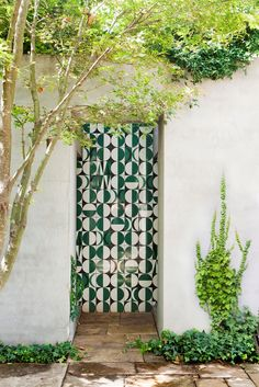 A geometric tiled wall catches the eye. The layered planting scheme also extends to the vertical surfaces in the garden. On the courtyard walls English ivy (*Hedera helix*) and Boston ivy (*Parthenocissus tricuspidata*) are planted together, with Asian jasmine (*Trachelospermum asiaticum*) spilling over from the top.: [object Object]
