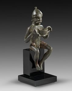 Roman Bronze Figurine of a Gaul, 1st-2nd Century ADDepicting a naked Gaul wearing only a helmet and holding a kantharos in his raised hands. The figure served probably as a water spout with water flowing from his mouth into the kantharos.