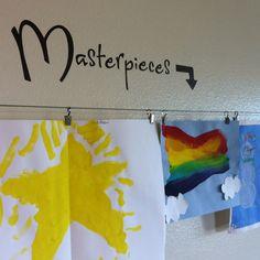 Kid art displayed using IKEA curtain rod.