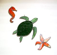 By the sea, by the sea, by the beautiful sea.  The shell of this lovely Green Sea Turtle is made with a textured, mottled green stained glass. The shell decoration is done with tinned wire. Decorative rippled solder outlines his shell  His flippers and head are a lovely sage green, textured glass.  The sea horse is made from a streaky orange glass, with a tiny millefiori at the tip of his tail.  White/ orange opal glass makes up the starfish. Finished with decorative solder  This trio can…