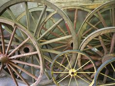 Antique Wooden Wagon Wheels Propped Against a Stucco Wall