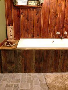 Rustic bathroom. Cedar focal wall, barn wood facing around tub. Tile flooring from Lowes.
