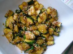 """Asian-Style Zucchini 1 tsp olive oil 1 clove garlic, grated 1"""" fresh ginger, grated 2 medium zucchini, quartered lengthwise and cut into ¼"""" slices 1 tbsp soy sauce 1 tbsp sesame seeds : Medium heat the oil, garlic and ginger and sauté about a minute. Add zucchini and increase heat to medium-high. Sauté zucchini about 5 min. Deglaze the pan with the soy sauce, sprinkle with sesame seeds, and serve."""