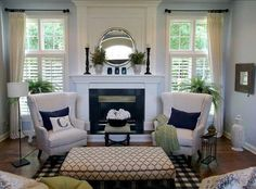 This very traditional living room feels much bigger than it is thanks to the use of a mirror above the fireplace and large windows on either side. Sophisticated navy and sage accents give this room a timeless feel. The monogrammed throw pillow on one of the wingback chairs in front of the fireplace makes it …