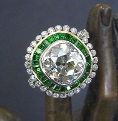 Important late Art Deco / 1940s Retro era diamond cluster ring comprising a large 5.30 carat old European modified cushion shape brilliant cut diamond, surrounded by 28 baguette cut natural and untreated rich and intense grass green demantoid garnet gems, further surrounded by pierced sunburst-like outer cluster of 28 smaller round brilliant diamonds.