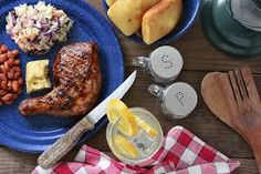 High angle shot of a barbecue chicken plate with cole slaw, pinto beans and corn bread. The meal is on a rustic wooden restaurant table with a red and white Cheap Bbq, Beans And Cornbread, Lamb Skewers, Chicken Plating, I Grill, Grilling, Barbecue Chicken, Pinto Beans, Coleslaw