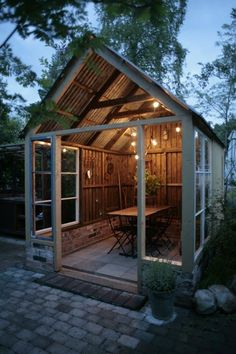 Make a backyard party shed like this one with a covered table for eating with guests and outdoor lights strung above for ambiance.