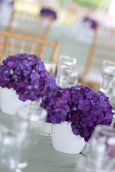 Purple hydrangeas in white ceramic vases on top of barely mint green linens.