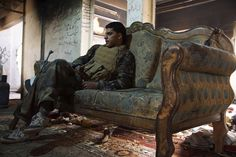 A rebel fighter sat on a sofa inside a house in Deir al-Zor May 13. Behind Enemy Lines with the Free Syrian Army, #WSJ