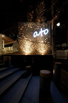 Cafe Ato by Design BONO, Seoul Gabion wall with floating stones. Night lighting sign.
