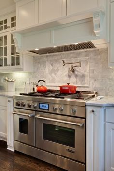 Great tile work with inset focal point over stove.  White marble and cabinetry