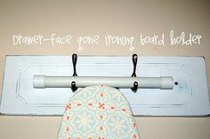Ironing board wall hanger... Front of a drawer with two hooks = snazzy ironing board hanger