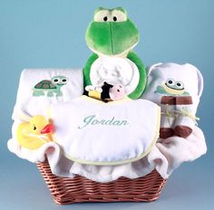 "Our Friendly Frog Baby Gift Basket is a wonderful way to send a very ""personal"" and thoughtful welcome to the world, whether it's a beautiful baby girl or a  precious baby boy.  The striking natural colored wicker basket is filled with quality layette items,  including a terry bib personalized with baby's name.  Each baby gift basket is made to order in the USA, beautifully presented,  and wrapped in tulle to make a big impression!"