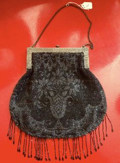 This Vintage French Style Beaded Purse with Fringe and Gold-toned Metal Frame is both delicate and mysterious. The shiny, tiny black and silver beads create a whimsical French floral pattern. The delicate gold-toned metal frame and aged chain balance out the slightly larger, round bottom of the purse.