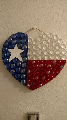 So proud of this Texas hanging decor that I made by painting a blank wooden heart. I used painting tape to separate the sections then purchased a wooden star to paint white. After that dried I used floral marbles that where clear, red, and blue each with a different finish. #diy #texas #wooden #decor #state #flag #heart #lovetexas #painted #hanging #handmade