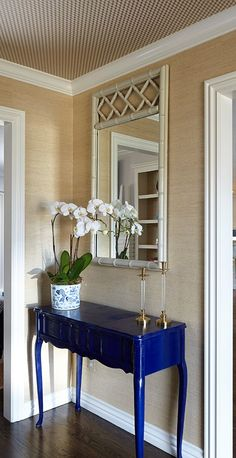 Chic foyer features walls clad in gold grasscloth lined with a blue lacquered console table with cabriole legs topped with lucite and brass candle holders under a gray bamboo mirror. Foyer Decorating, Interior Decorating, Interior Design, Wallpaper Ceiling, Grass Cloth Wallpaper, Wallpaper Staircase, Foyer Wallpaper, Painted Furniture, Furniture Design