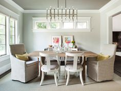 Elegant dining room with Jonathan Adler Meurice Rectangular Chandelier hung from dark gray ceilings over a simple wooden dining table lined with contemporary white side chairs and a pair of slipcovered linen captain chairs accented with yellow pillows over hardwood floors layered with a sisal rug.